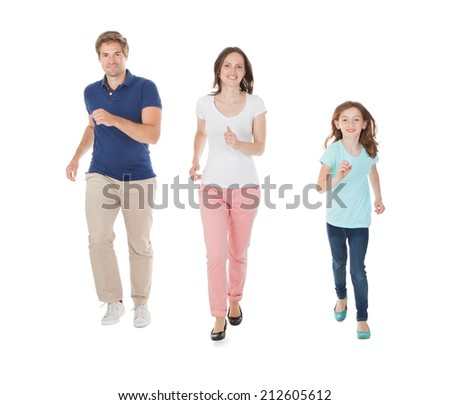 Full length portrait of happy family running against white background - stock photo