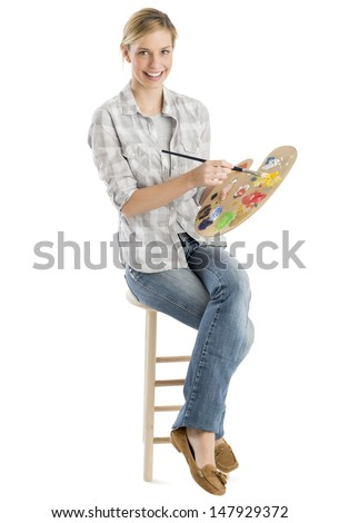 Full length portrait of happy female artist with palette and paintbrush sitting on stool against white background - stock photo