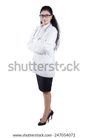 Full length portrait of happy female doctor standing in coat smiling at camera - stock photo