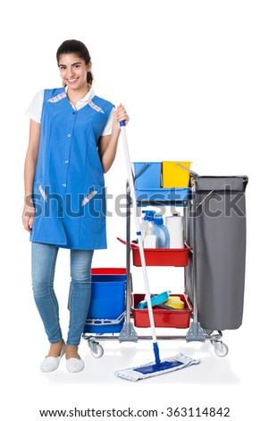 Full length portrait of happy female janitor mopping by trolley on white background - stock photo