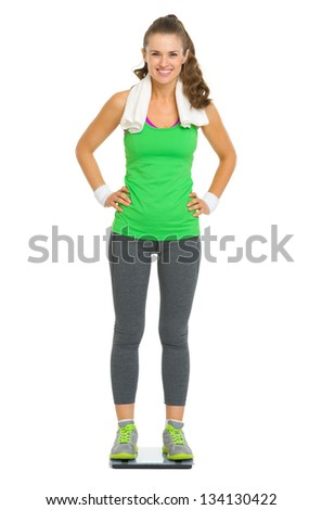 Full length portrait of happy fitness young woman standing on scales - stock photo
