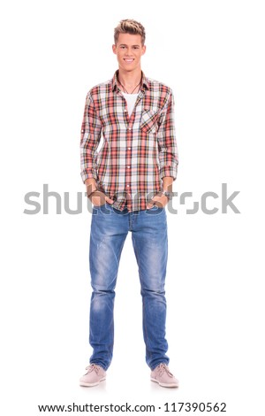 Full length portrait of happy handsome casual young man standing with his hands in his pockets isolated on white background - stock photo