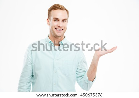Full length portrait of happy handsome confident cheerful attractive young man holding copyspace on the palm over white background - stock photo