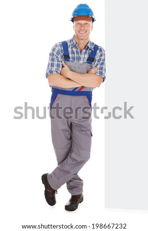 Full length portrait of happy manual worker standing arms crossed over white background