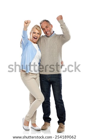 Full length portrait of happy mature couple cheering on white background - stock photo