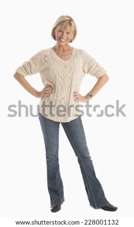 Full length portrait of happy mature woman in casuals with hands on hip over white background - stock photo