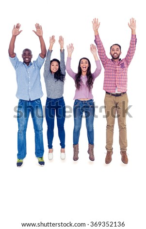 Full length portrait of happy multi-ethnic friends jumping with arms raised against white background