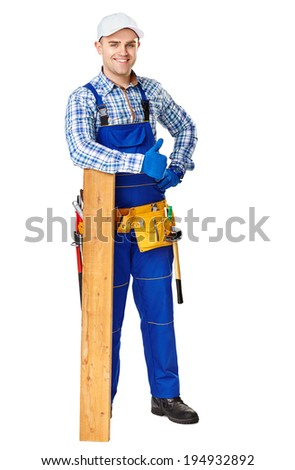 Full length portrait of happy young carpenter leaning on a wooden plank and showing thumbs up gesture isolated on white background
