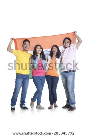 Full length portrait of happy young friends in casuals holding Indian flag over white background