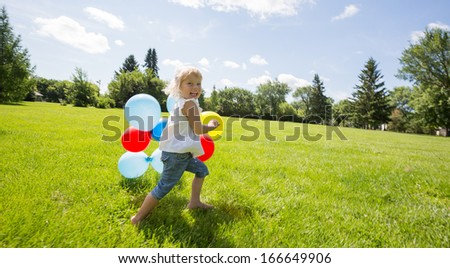 Full length portrait of happy young girl with colorful balloons running in grassy meadow - stock photo
