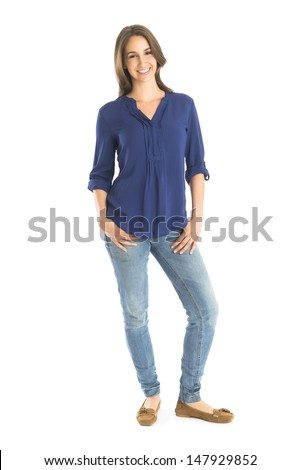 Full length portrait of happy young woman standing with hands in pockets against white background - stock photo