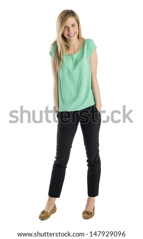Full length portrait of happy young woman with hands in pockets standing against white background