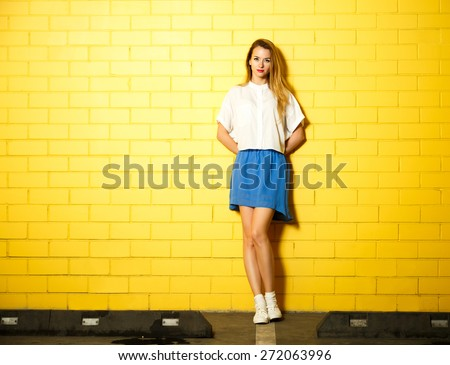 Full Length Portrait of Hipster Fashion Girl with Hands behind her Back Standing at the Yellow Brick Wall Background. Youth Urban Fashion Concept. Copy Space. - stock photo