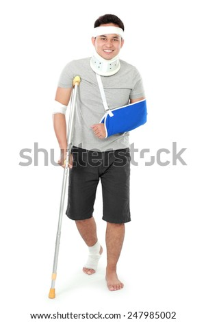 full length portrait of  injured young man on crutch - stock photo
