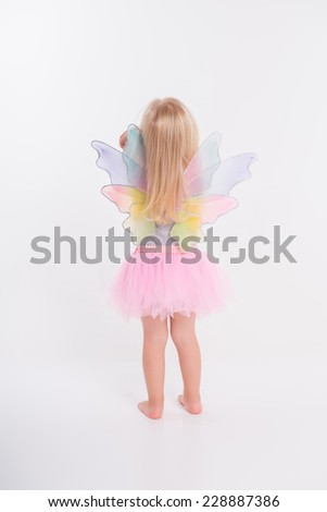 Full-length portrait of little fair-haired lovely girl wearing pretty grey vest and pink skirt standing back taking offence at us. Isolated on white background - stock photo