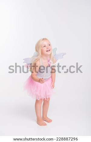Full-length portrait of little fair-haired lovely girl wearing pretty grey vest pink skirt and white wings standing with her magic wand and laughing. Isolated on white background