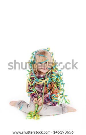 Full length portrait of little girl wrapped with ribbons while sitting isolated over white background