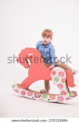 Full-length portrait of little lovely smiling girl wearing blue shirt and brown pants climbing up on the pink wooden toy horse. Isolated on the white background - stock photo