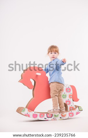 Full-length portrait of little lovely smiling girl wearing blue shirt and brown pants standing on the pink wooden toy horse and pointing at us. Isolated on the white background - stock photo