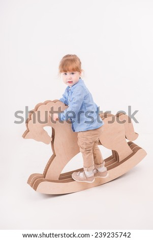 Full-length portrait of little lovely smiling girl wearing blue shirt and brown pants swaying on the wooden toy horse looking at us. Isolated on the white background - stock photo