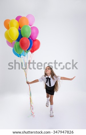 Full length portrait of little school girl standing with balloons isolated on a white background - stock photo