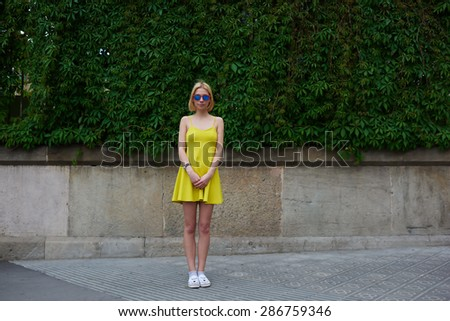 Full length portrait of lovely young woman in summer bright dress posing on nature fence background in city, female cute hipster girl standing against blank copy space for your text message or content - stock photo