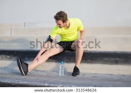 Full length portrait of male runner touching pulled leg muscle as a result of fitness training outdoors, young sportsman taking break after get injured in the middle of morning running outside of city - stock photo