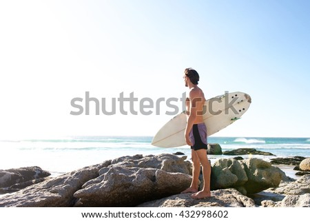 Full length portrait of male surfer looking at the sea - stock photo