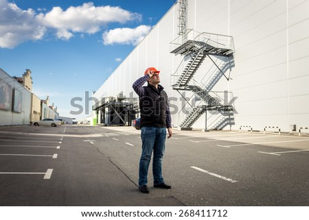 Full length portrait of male worker posing on parking of industrial building - stock photo
