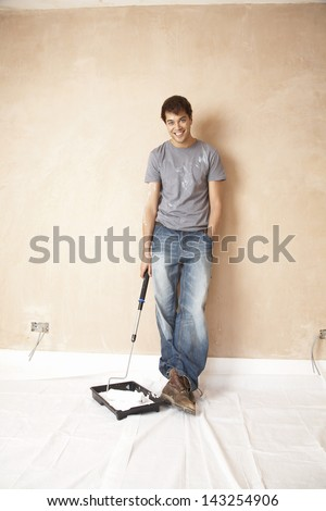 Full length portrait of man dipping paint roller in paint at unrenovated house - stock photo