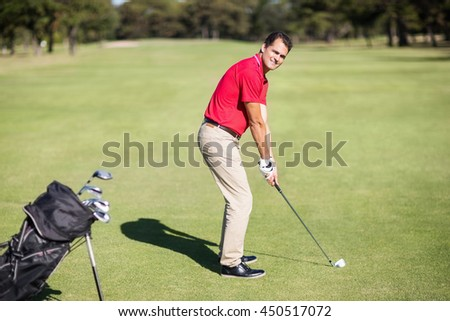 Full length portrait of man playing golf while standing on field - stock photo