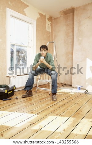 Full length portrait of man sitting on step ladder while holding coffee mug in unrenovated room - stock photo