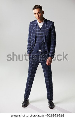 Full length portrait of man wearing suit, one hand in pocket - stock photo