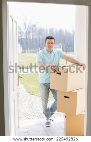 Full-length portrait of man with stacked cardboard boxes at new house - stock photo