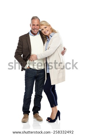 Full length portrait of mature couple standing together on white background - stock photo