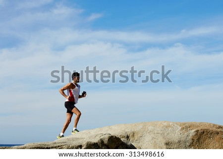 Full length portrait of mature male jogger running up the rocks against blue sky background with copy space area for text message, sports man training outdoors while listening to music in headphones