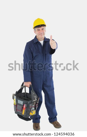 Full length portrait of mature mechanic with tool bag showing thumbs up sign over white background - stock photo
