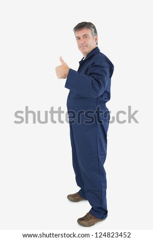 Full length portrait of mature technecian gesturing thumbs up sign over white background - stock photo