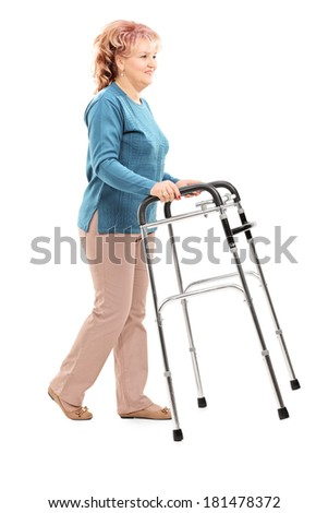 Full length portrait of mature woman walking with walker isolated on white background