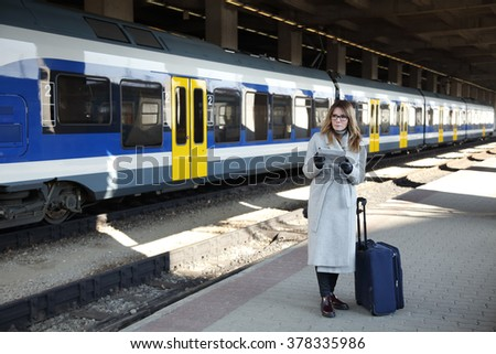 Full length portrait of middle age businesswoman holding in her hand a digital tablet and checking timetable while waiting for the train at the station.  - stock photo