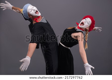 Full-length portrait of mime couple wanting to hug each other, female mime looking at the camera, male mime laughing and looking at his girlfriend isolated on grey background with copy place - stock photo