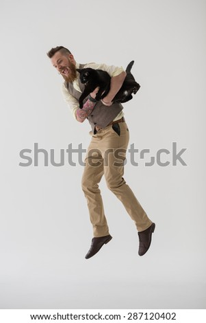 Full length portrait of modern groom jumping with his cat - stock photo