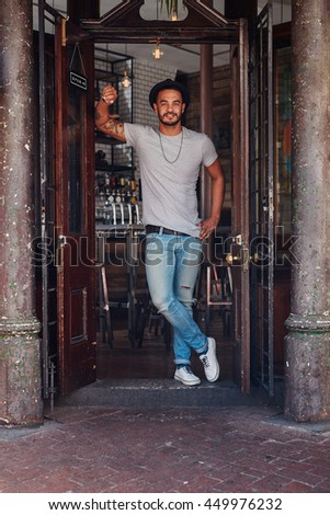 Full length portrait of modern young male standing at the entrance of a coffee shop. Stylish young man at a cafe front door. - stock photo