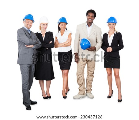 Full length portrait of multiethnic architects with hardhats standing against white background - stock photo