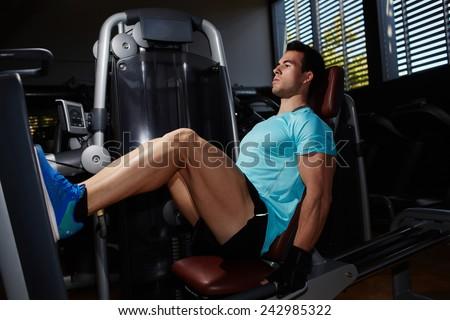 Full length portrait of muscular build man doing legs press exercise in fitness center - stock photo