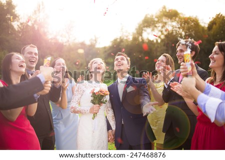 Full length portrait of newlywed couple and their friends at the wedding party showered with confetti in green sunny park - stock photo
