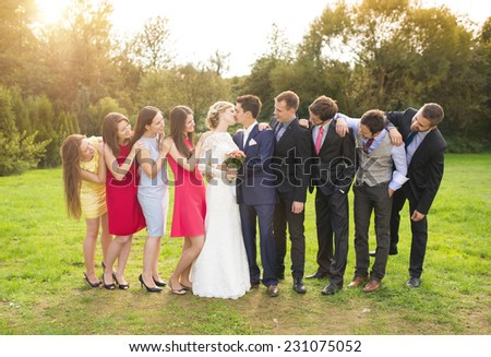 Full length portrait of newlywed couple kissing posing with bridesmaids and groomsmen in green sunny park - stock photo