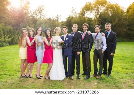Full length portrait of newlywed couple posing with bridesmaids and groomsmen in green sunny park - stock photo