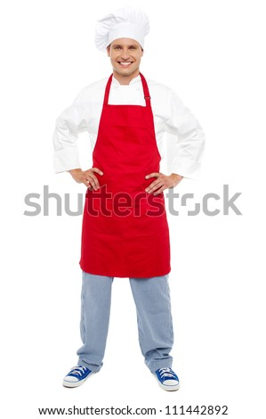 Full length portrait of relaxed chef standing with hands on his waist - stock photo