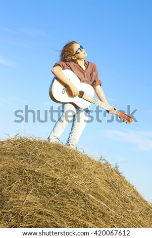 Full length portrait of relaxed cow girl wear dark sunglasses Cute woman standing on the haystack on blue sky with clouds background Good weather with wind Empty copy nature space for inscription - stock photo